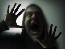 Verärgerter Mann hinter dem Glas Stockbild