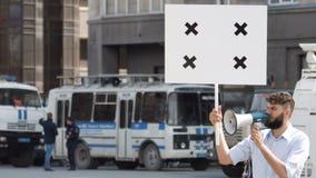 Verärgerter Mann schreit in ein Megaphon auf Streik Ärger und Raserei in den Leuten