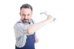Verärgerter Mechaniker, der mit einem Stahlschlüssel heftig fungiert stockbilder
