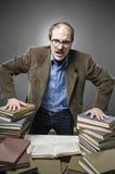 Verärgerter Professor mit einem Stapel Büchern lizenzfreie stockfotos