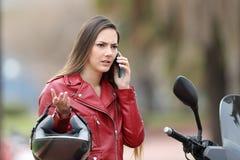 Verärgerter Radfahrer, der Versicherung am Telefon nennt stockbild