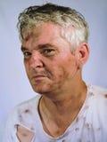 Verärgerter schmutziger älterer Mann in zerrissenem T-Shirt Lizenzfreies Stockfoto