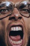 Verärgerter schreiender Mann in den alten Gläsern Stockfoto