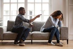 Verärgerter schwarzer Ehemann, der umgekippte Frau von Problemen tadelnd argumentiert lizenzfreie stockfotografie