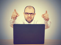 Verärgerter an seinem Schreibtisch sitzender und schreiender Geschäftsmann Stockfoto