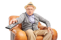 Verärgerter Senior, der Knöpfe auf einer Fernbedienung bedrängt Stockfoto