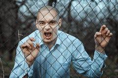 Verärgerter und ängstlicher Mann, der über der Zaunmasche grinst Lizenzfreie Stockbilder