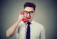Verärgerter wütender Geschäftsmann, der am Telefon schreit stockbild