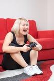 Verärgertes blondes Mädchen, das Videospiele spielt Stockfoto