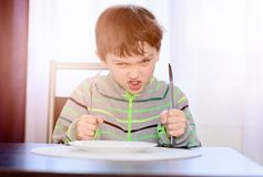 Verärgertes hungriges Jungenkinderwarteabendessen Stockfotos