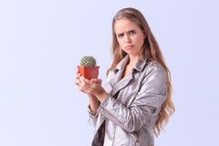 Verärgertes junges Mädchen, das mit Kaktus auf einem grauen Hintergrund aufwirft Stockbild