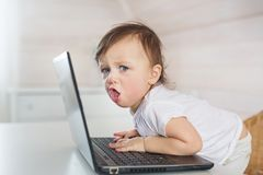 Verärgertes kleines Baby mit einem Laptop stockbild