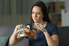 Verärgertes Mädchen, das ein Paarfoto nach Auseinanderbrechen bricht lizenzfreies stockbild