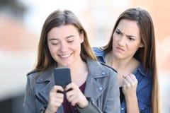 Verärgertes Mädchen, welches das Telefon eines Freunds ausspioniert lizenzfreies stockbild
