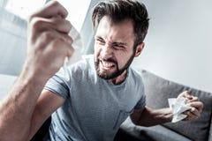 Verärgertes zerknitterndes Papier des jungen Mannes Stockfoto