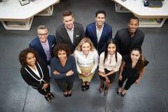 ?ver huvudet st?ende av aff?ren Team Standing In Modern Office royaltyfri bild