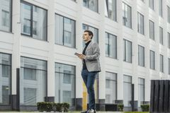 Ver plan van de jonge bedrijfsmens die mobiele telefoon naast commercieel centrum houden royalty-vrije stock afbeeldingen