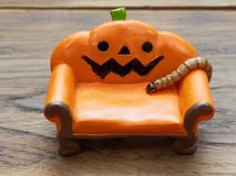 Ver superbe ou géant rampant sur le divan ou le sofa en céramique miniature orange de potiron au-dessus de la surface en bois fon image libre de droits