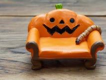 Ver superbe ou géant rampant sur le divan ou le sofa en céramique miniature orange de potiron au-dessus de la surface en bois fon images libres de droits