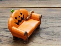 Ver superbe ou géant rampant sur le divan ou le sofa en céramique miniature orange de potiron au-dessus de la surface en bois fon photo stock