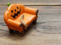 Ver superbe ou géant rampant sur le divan ou le sofa en céramique miniature orange de potiron au-dessus de la surface en bois fon photographie stock