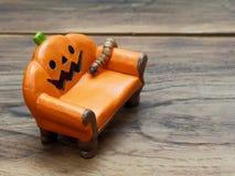 Ver superbe ou géant rampant sur le divan ou le sofa en céramique miniature orange de potiron au-dessus de la surface en bois fon images stock