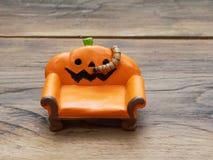 Ver superbe ou géant rampant sur le divan ou le sofa en céramique miniature orange de potiron au-dessus de la surface en bois fon photos libres de droits