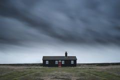 Ver troosteloos geïsoleerd huis onder donkere stormachtige hemel tijdens Wint royalty-vrije stock foto's