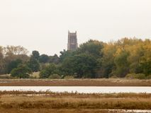 Ver van donkere de rivierkust van de kerk hoogste spits Stock Afbeelding
