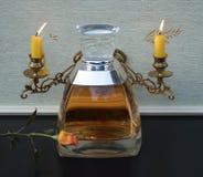 Vera Wang, Duft für Damen, große Parfümflasche vor Kandelaber mit den glänzenden Kerzen verziert mit einer englischen Rose lizenzfreie stockfotos