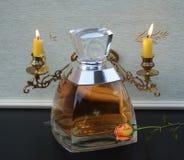 Vera Wang, Duft für Damen, große Parfümflasche vor Kandelabern eines Klaviers mit den glänzenden Kerzen verziert mit einer Rose lizenzfreie stockfotografie