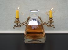 Vera Wang, Duft für Damen, große Parfümflasche vor Kandelabern eines Klaviers mit glänzenden Kerzen lizenzfreie stockfotos