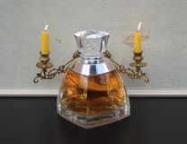 Vera Wang, fragrance for ladies, large perfume bottle in front of a piano candelabra with shining candles royalty free stock photography