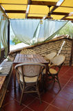 Veranda with drapes and sea view. Wooden table and chairs, veranda with drapes and sea view. Mediterranean architecture Royalty Free Stock Photography