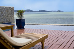 Veranda with an ocean view. A beautiful decorated veranda with deck chairs with an ocean view Royalty Free Stock Photos