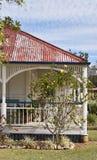 Veranda på gamla Queenslander med det urblekta röda metalltaket royaltyfri bild