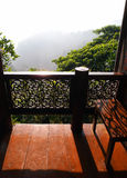 Veranda with view, thai house. A photograph showing the wooden verandah of a old thai style house in the morning sunlight, with a beautiful misty view over the Royalty Free Stock Photos