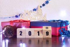 Verandering van jaar op houten kubussen op de achtergrond van giftdozen en vakantiedecoratie stock afbeelding