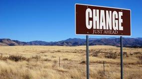 Veranderings enkel vooruit bruine verkeersteken stock foto