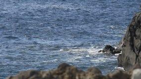Veranderlijke golven die van blauwe overzees rotsen, klippen raken die uit water, langzame motie te voorschijn komen stock footage
