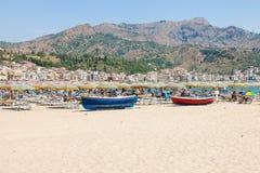 Veraneantes y barcos en la playa en Giardini Naxos Imágenes de archivo libres de regalías