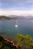 Verankerd jacht bij mooie kust Stock Foto