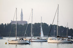 Verankerte Segelboote vor Heiliges Euphemia-Glockenturm Stockfoto