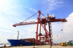 Verankertes Containerschiff und Kräne in einem Hafen lizenzfreie stockfotos
