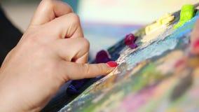 Verano, al aire libre, el primer de las manos femeninas del artista y una paleta con las pinturas, el artista mezcla las pinturas metrajes