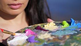 Verano, al aire libre, el primer de una paleta con las pinturas, el artista de la mujer mezcla las pinturas con un cepillo en la  metrajes