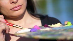 Verano, al aire libre, el primer de una paleta con las pinturas, el artista de la mujer mezcla las pinturas con un cepillo en la  almacen de metraje de vídeo