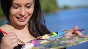 Verano, al aire libre, retrato de un artista moreno hermoso de la mujer de cuarenta años, primer de una paleta con las pinturas, almacen de metraje de vídeo