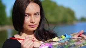 Verano, al aire libre, retrato de un artista moreno hermoso de la mujer de cuarenta años, primer de una paleta con las pinturas, metrajes