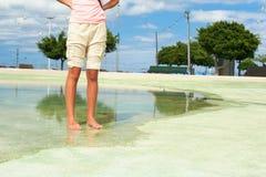 Verano caliente en la ciudad Piernas adolescentes y pies mojados en agua Imágenes de archivo libres de regalías